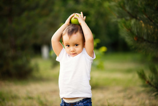 .Little child in white shirt holding a green apple on his head. Toddler boy with an apple outdoor near pine tree.