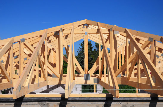 Roofing Construction. Wooden roof frame house construction  with wooden roof beams, trusses, timber.