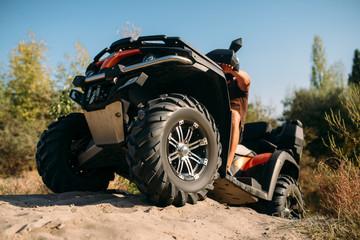 Atv rider climbing the sand mountain in quarry