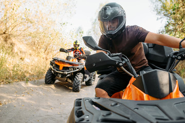 Papiers peints Motorise Two quad bike riders travels in forest, front view
