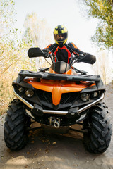 Rider in helmet on quad bike, front view, closeup