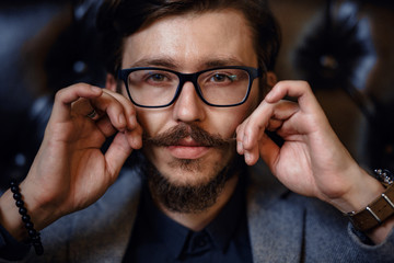 Stylish man puts himself in order. Guy straightens his mustache
