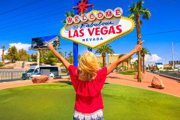Carefree woman with raised arms at Welcome to Fabulous Las Vegas Nevada Sign, popular landmark on Las Vegas Strip at entrance of the city. Happy tourist in Nevada, Unites States. Blue sky.