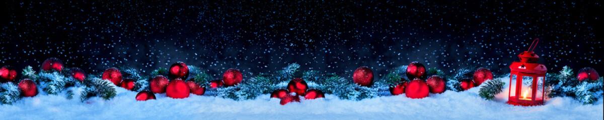 Laterne mit Weihnachtskugeln und Tannenzweig vor dunklem Hinterdrund mit Schnee