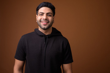 Young handsome Indian man against brown background