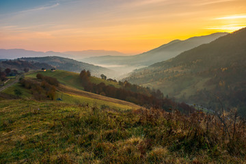 beautiful mountainous countryside at dawn. village on the hill and in valley full of fog. wonderful autumn landscape