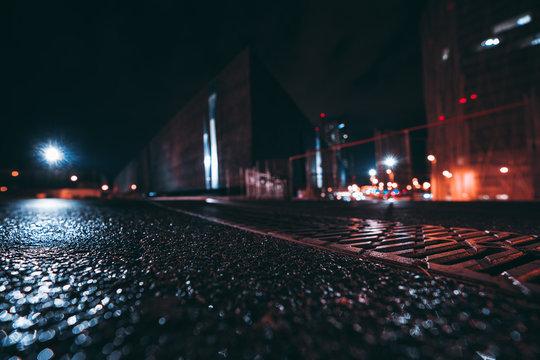 Wide-angle abstract shot from the ground of night cityscape with shallow depth of field and selective focus on the foreground, strong bokeh from a wet asphalt, flares from streetlights, Barcelona