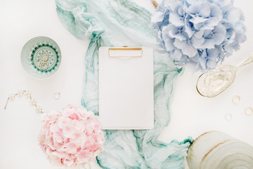 Clipboard with copy space, turquoise blanket, colorful pastel hydrangea flower bouquet, woman fashion accessories on white background. Flat lay, top view mockup.