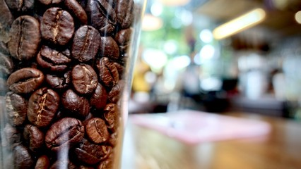 Cafe and restaurant decorated by a clear glass with coffee bean inside on the table, atmosphere cafe and people background