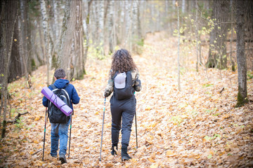 Nordic walking. Little boy and young woman. Back view