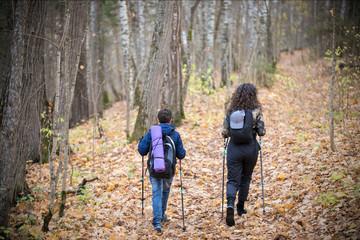 Nordic walking. Little boy and young woman. Back view. Fall season