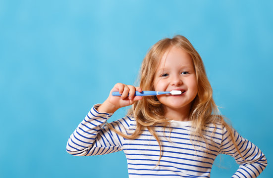 A little girl in striped pajamas is brushing her teeth with a toothbrush. The concept of daily hygiene. Isolated on a blue background