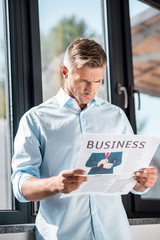 serious adult businessman reading business newspaper in front of window