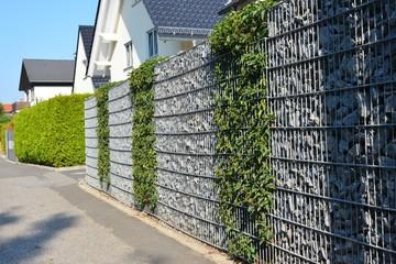 Moderner Sichtschutzzaun aus mit Naturstein gefüllten Gabionen und eingegrüntem verzinktem Stahlgitter um ein bebautes Grundstück