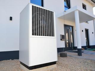 Luftwärmepumpe für Heizung und Warmwasser vor einem neuen modernen Einfamilienhaus