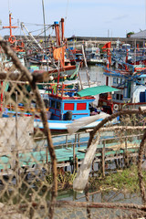 View past lobster pots to a vintage brightly colored wooden fishing boat docked in a harbor in south east Asia