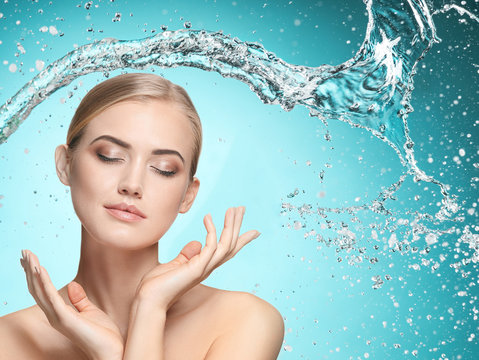 Beautiful woman with splashes of water in her hands. Beautiful girl under splash of water with fresh skin on blue background. Skin care, cleansing and moisturizing concept. Beauty face