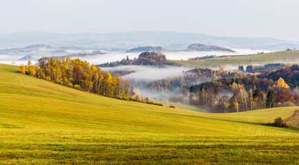 View of autumn mountain hills, colorful meadows, trees and fields. Rural remote location, villages and forests. Fog and haze. Outdoor and adventure.