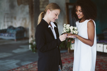 Young pretty woman with blond hair in black suit putting a wedding ring on beautiful african american woman with dark curly hair in white dress on wedding