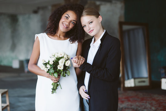 Young pretty woman with blond hair in black suit and beautiful african american woman with dark curly hair in white dress with little bouquet of flowers happily looking in camera on wedding
