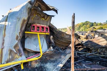 Burned damaged ruins of destroyed supermarket metallic facade arson investigation insurance