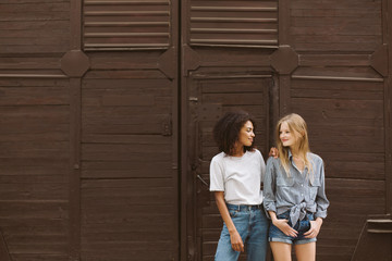 Young nice african american woman with dark curly hair in T-shirt and jeans and pretty woman with blond hair in shirt and shorts happily looking at each other with brown wall on background