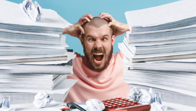 Frustrated overwhelmed executive working in the office and overloaded with paperwork, he is screaming and feeling depressed