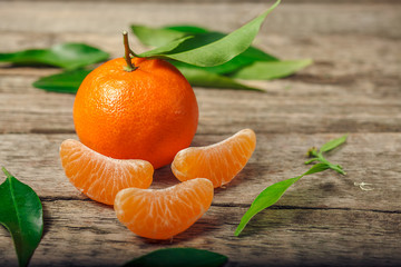 Tangerines oranges, clementines, citrus fruits with green leaves over wooden background with copy space
