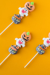 Halloween candies arranged in an alternating pattern on an colored background