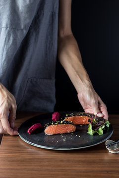 Woman preparing delicious candied salmon fillets
