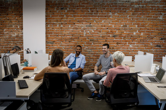 Businesswomen and businessmen sitting together at open space office and talking.