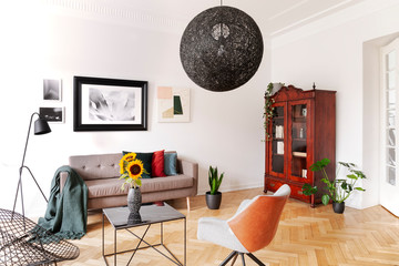 Sunflowers on table between armchair and sofa in flat interior with lamp and posters. Real photo