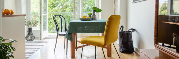 Panoramic view of stylish yellow chair next to table covered with green tablecloth in modern kitchen with balcony