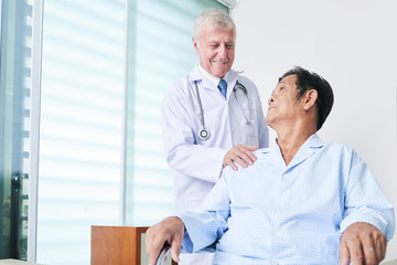 Elderly man in doctor uniform smiling and supporting senior Asian man while standing in ward of modern clinic