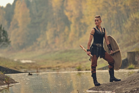 Viking woman with axe in a traditional warrior clothes. Against the backdrop of a large viking village