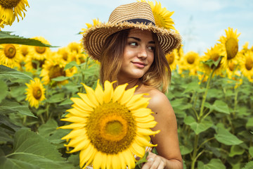 Young woman with a straw hat smiling in a field of sunflowers