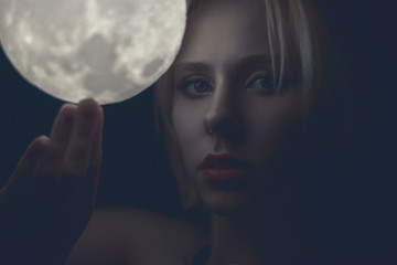 Woman holding a glowing sphere moon. Toned in warm color.