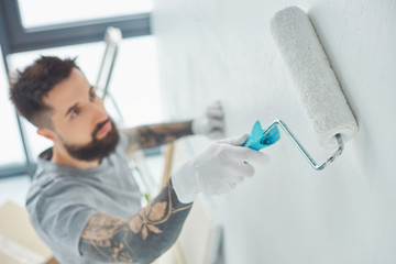 selective focus of tattooed repairman with roll paint brush painting wall in new apartment