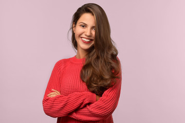 Studio isolated portrait of a young beautiful student girl with long dark hair. She smiles warmly and looks into the camera. Her arms folded across her chest