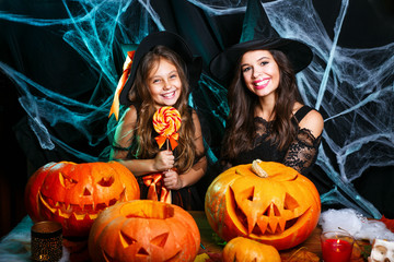 Happy Halloween. Beautiful caucasian mother and her daughter in witch costumes celebrating Halloween with Halloween candy and sweet over spider web Wall mural