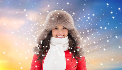 people, season and leisure concept - happy woman in winter fur hat outdoors over sky background and snow