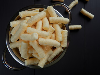 Crunchy, salty corn puffs snacks, also known in Romanian as pufuleti, in a red strainer, on dark brown background