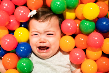 Portrait of a adorable infant on colorful balls dont have fun