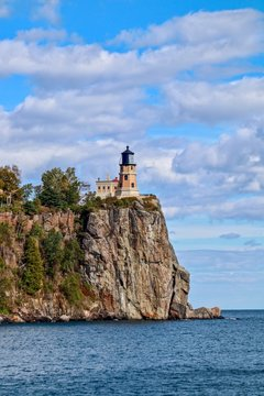 Split Rock Lighthouse on Lake Superior with blue sky and white clouds