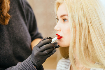 Young beautiful blond woman applying make-up,painting red lips by make-up artist.