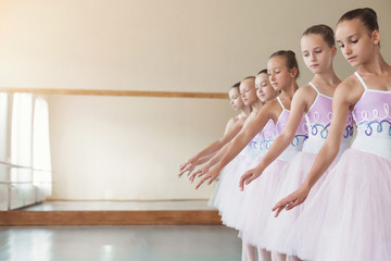 Ballerinas standing in row and exercising in class