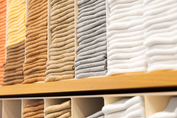 shopping, sale and retail concept - close up of shelves with clothes at clothing store