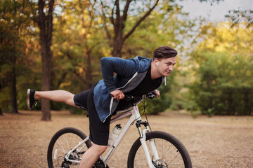 Attractive young caucasian man with dark hair bicycling in the park. White earphones, favorite music. Outdoors, golden leaves. Early autumn / fall background. Healthy life sport, fitness. Copy space