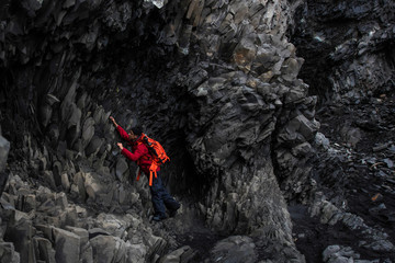Male tourists are climbing lava rock at Black Sand in Iceland.