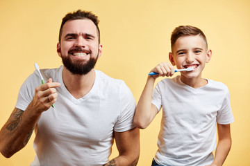 happy father and son holding toothbrushes and smiling at camera on yellow background